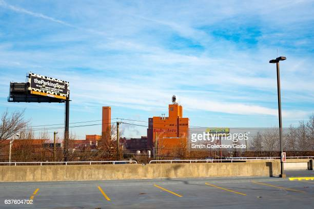 Budweiser beer factory viewed from across an empty parking lot, with a billboard for ParkingSpot, Newark, New Jersey, December 21, 2016. .