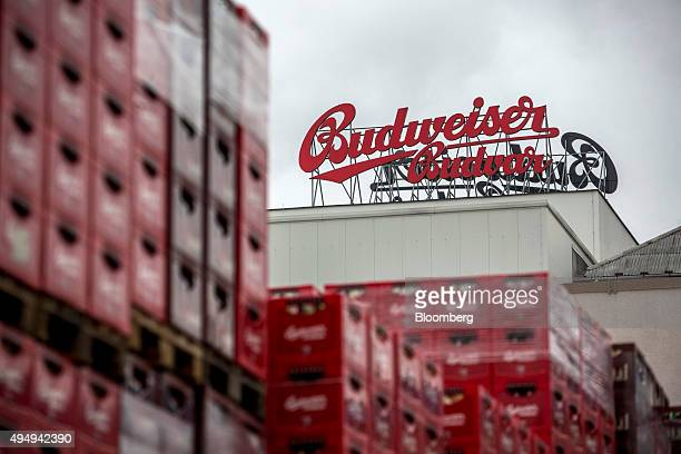 A Budweiser Budvar logo sits above a building beyond crates of beer awaiting distribution at the Budejovicky Budvar NP production plant in Ceske...
