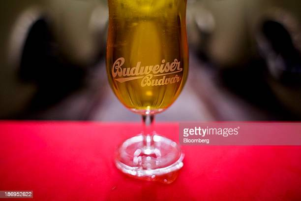 A Budweiser Budvar logo sits in a glass of beer arranged for a photograph in the storage cellar at the headquarters of Budejovicky Budvar NP the...
