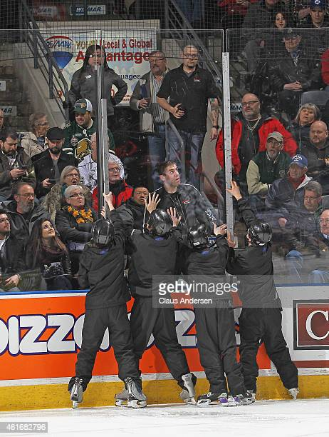 Budweiser Gardens ice crew replace a piece of glass during a play stoppage between the Windsor Spitfires and the London Knights in an OHL game at...