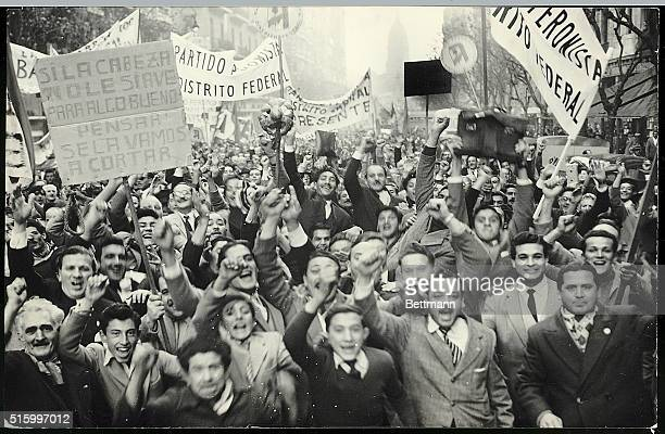 Buenos Aires Argentina A crowd of Peronist supporters shout and raise their fists under banners during demonstrations Ca 1950