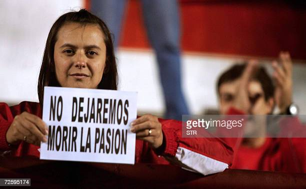 A fan of Argentinos Juniors holds a sign that reads We Won't Let The Passion Die during the match between her team and Independiente held at...