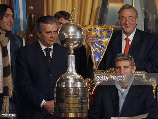Argentina's President Nestor Kirchner shows a Boca Junior's pennant during a meeting at the presidential house Casa Rosada with the Argentina's Boca...