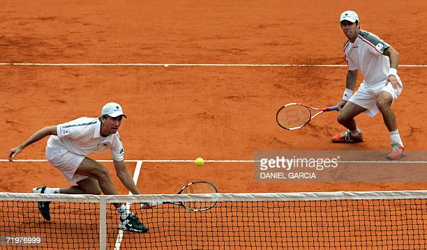 Australian Wayne Arthurs hits a volley as teammate Paul Hanley looks on during their Davis Cup tennis tournament semifinal doubles match game against...