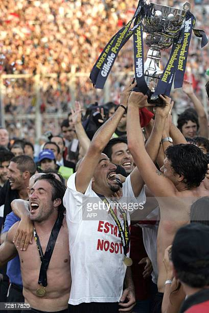 Estudiantes' team captain Juan Veron holds the trophy between striker Mariano Pavone and other players at the end of the final match of the Argentine...
