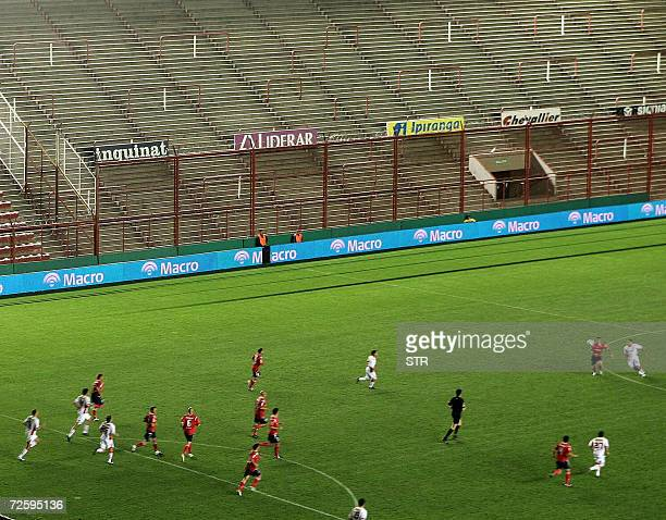 Footballers of Argentinos Juniors and Independiente vie for the ball before an empty grandstand at Argentino Junior's Diego Maradona stadium in...
