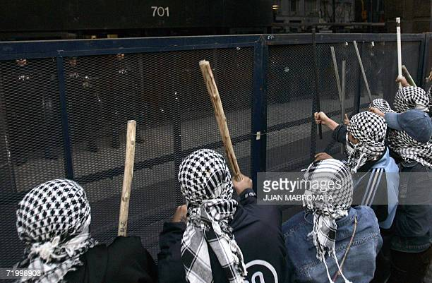 Hooded demonstrators bang a police fence during a protest of the Islamic community against Israel's offensive against Hezbollah and Hamas in Lebanon...