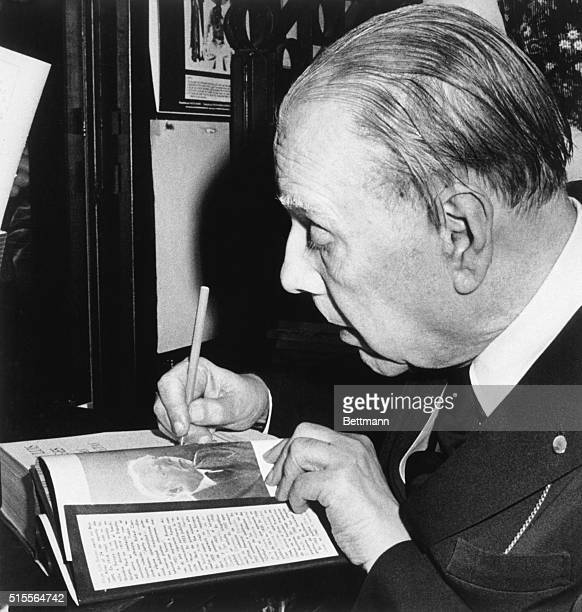 Buenos Aires, Argentina: Jorge Luis Borges, Argentina's best known author, autographs one of his books. Borges, who recently celebrated his 85th...