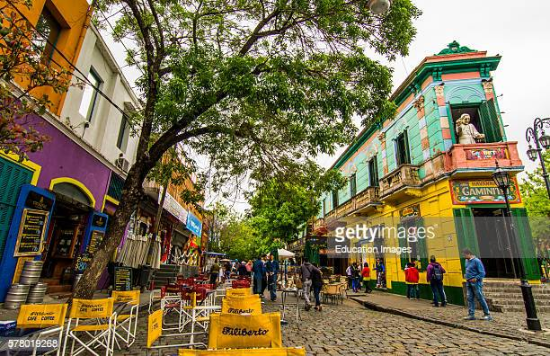Buenos Aires Argentina La Boca colorful streets and buildings with tourists on corner with shops and restaurants with bright primary colors