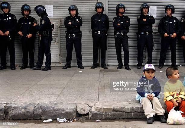 Ninos bolivianos escuchan el discurso de dirigentes el 05 de marzo de 2006 mientras la policia custodia locales cerrados durante una manifestacion en...