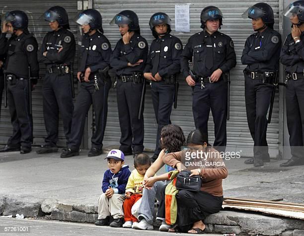Buenos Aires, ARGENTINA: Una familia de ciudadanos bolivianos escuchan el discurso de dirigentes el 05 de marzo de 2006 mientras la policia custodia...