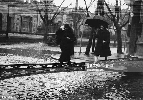 """Buenos Aires im Regen"""" - zwei Frauen gehen über eine improvisierte Brücke, die über eineübeschwemmte Strasse in Buenos Aires führt- August 1930"""