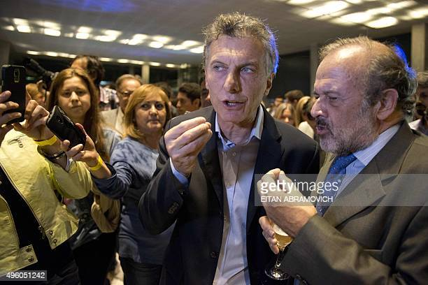 Buenos Aires Mayor and presidential candidate for the Cambiemos party Mauricio Macri speaks with a supporter during the inauguration of a convention...