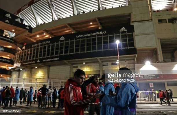 Buenos Aires police cadets check on their cell phones the ID card of supporters of River Plate at the entrance of the Monumental stadium before the...
