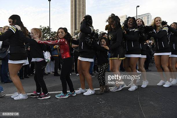 Buff fans line dance with Colorado cheerleaders during rally near the Alamodome for the Valero Alamo Bowl against the Oklahoma State Cowboys December...