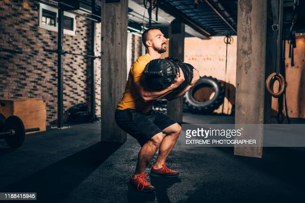 buff male athlete doing core bag squats exercise in a gym - sandbag stock pictures, royalty-free photos & images