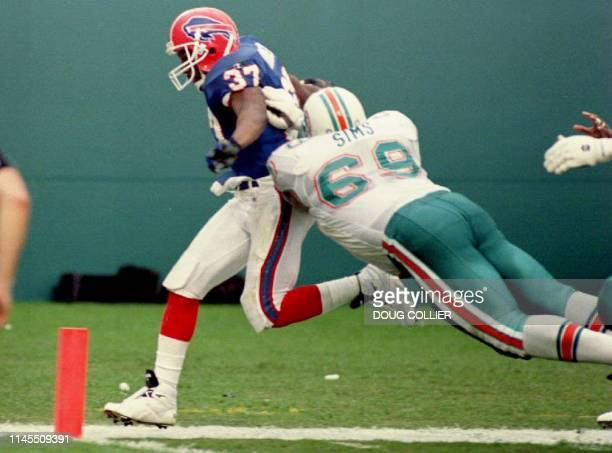 Buffalo Bills defensive back Nate Odomes evades a diving tackle by Miami Dolphins offensive guard Keith Sims to score a touchdown 19 December 1993 in...