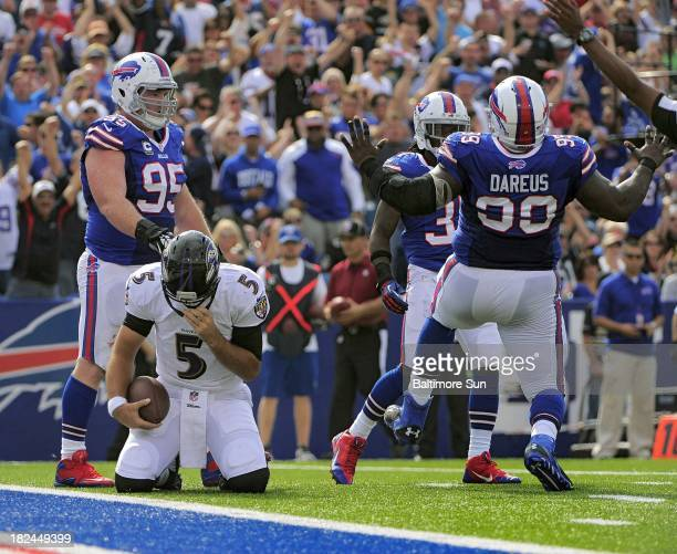 Buffalo Bills defensive tackle Kyle Williams stands behind Baltimore Ravens quarterback Joe Flacco watching Bills defensive tackle Marcell Dareus...