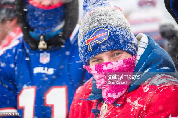 Buffalo Bills fans bundled in winter apparel watch action between the Buffalo Bills and the Indianapolis Colts as snow falls at New Era Field on...