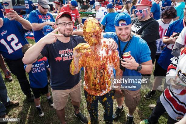 Buffalo Bills fans pose for a picture with Ken Johnson after the ketchup and mustard shower while tailgating at the Hammer's Lot at the Pinto Ron...