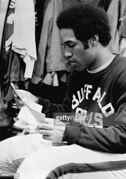 Buffalo Bills' OJ Simpson takes a few minutes to read a few Christmas cards in the Bills dressing room after the morning practice at Rich Stadium...