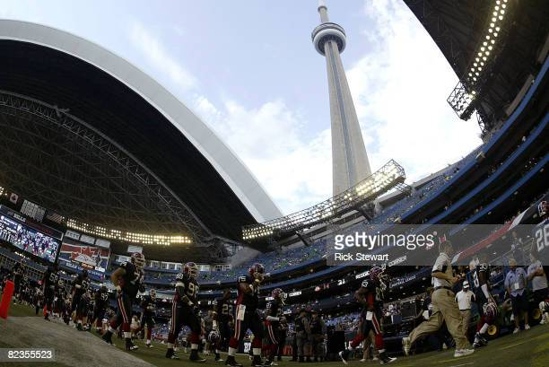 Buffalo Bills players leave the field after warming up with the Pittsburgh Steelers as the dome roof begins to close with the CN Tower in the...