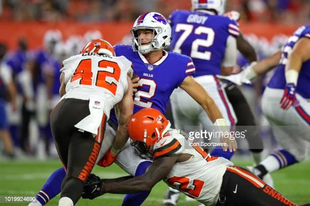 Buffalo Bills quarterback Nathan Peterman is sacked by Cleveland Browns linebacker Justin Currie and Cleveland Browns linebacker James Burgess Jr...