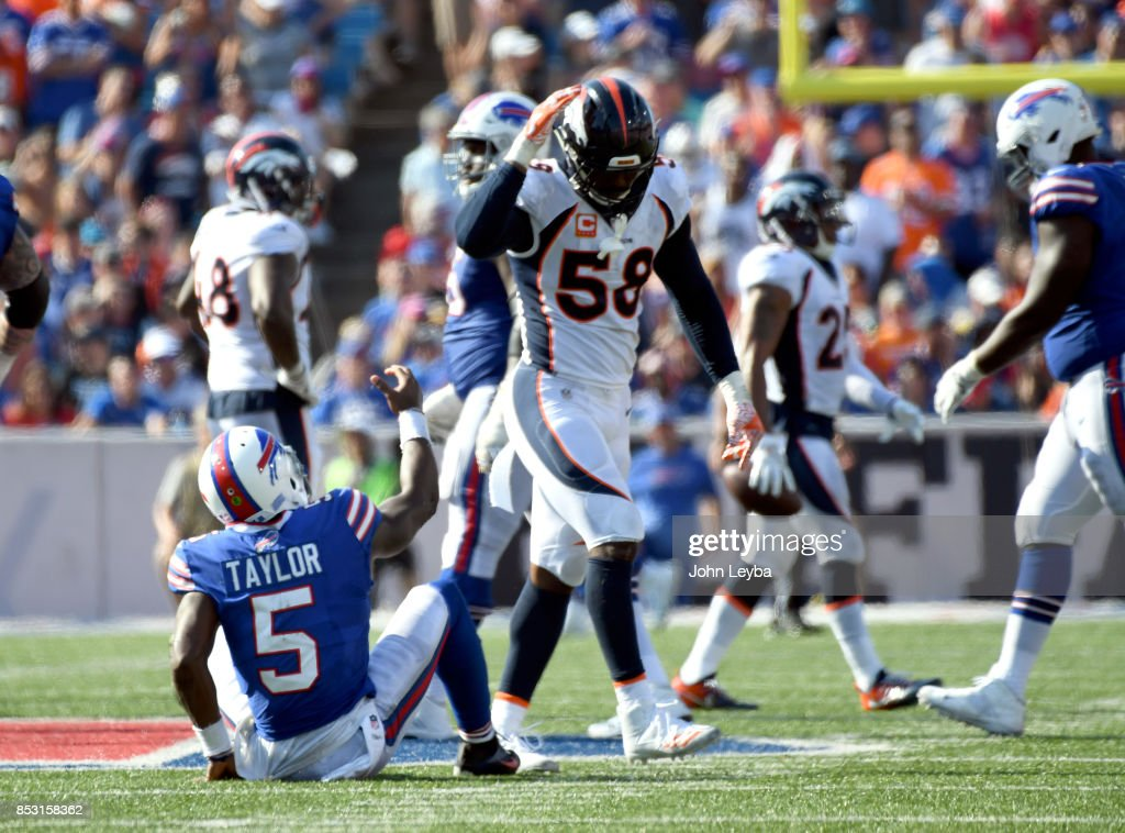 Buffalo Bills quarterback Tyrod Taylor (5) sits on the turf after getting hit by Denver Broncos outside linebacker Von Miller (58) during the fourth quarter on September 24, 2017 at New Era Field in Orchard Park, NY. After the play, Miller pretends to help Bills quarterback Tyrod Taylor up, but pulls back his hand as a joke. Miller was flagged on the play for un-sportman like conduct.