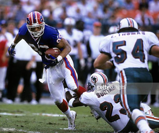 Buffalo Bills wide receiver Andre Reed tries to get away from Miami Dolphins defensive back Patrick Surtain as linebacker Zack Thomass zeroes in...