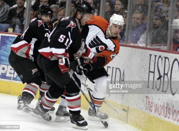 Buffalo Sabres' Brian Campbell battles Flyer's RJ Umberger for the lose puck during a game versus the Philadelphia Flyers at the HSBC Arena in...