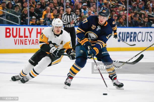 Buffalo Sabres center Casey Mittelstadt skates with puck as Pittsburgh Penguins center Evgeni Malkin defends during the Pittsburgh Penguins and...