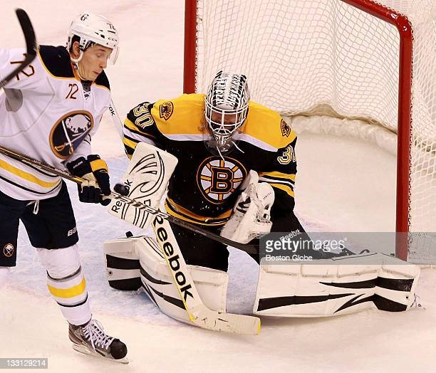 Buffalo Sabres center Luke Adam tries to get his stick on the puck for a redirection as Boston Bruins goalie Tim Thomas eyes the puck The Boston...