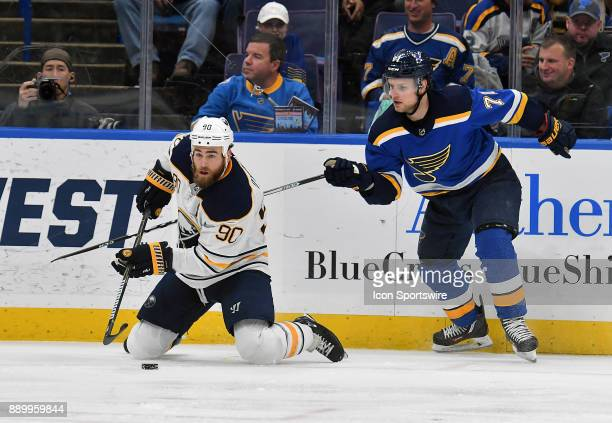 Buffalo Sabres center Ryan OReilly falls to his knees ahead of St Louis Blues left wing Vladimir Sobotka as he goes for the puck during a NHL game...