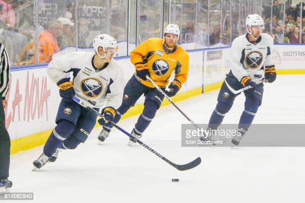 Buffalo Sabres Defenseman Erik Autio skates with the puck as Buffalo Sabres Center Sean Malone looks on during the French Connection Tournament at...