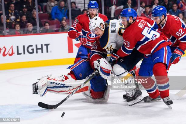 Buffalo Sabres defenseman Nathan Beaulieu battles to get possession of the puck while being cut in between Montreal Canadiens goalie Charlie Lindgren...