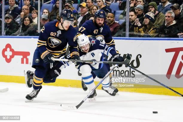 Buffalo Sabres Defenseman Nathan Beaulieu skates towards puck as Winnipeg Jets Center Bryan Little defends and Buffalo Sabres Defenseman Zach...