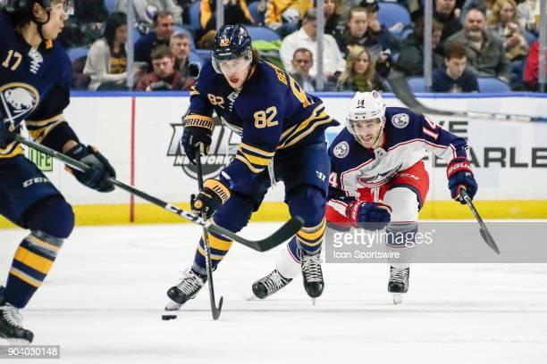Buffalo Sabres Defenseman Nathan Beaulieu skates with the puck as Columbus Blue Jackets Center Jordan Schroeder prepares to back check during the...