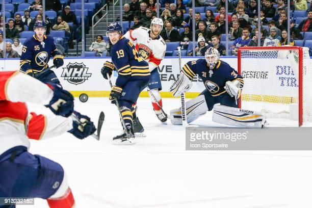 Buffalo Sabres Goalie Chad Johnson prepares to make save on shot as Buffalo Sabres Defenseman Jake McCabe Buffalo Sabres Defenseman Rasmus...