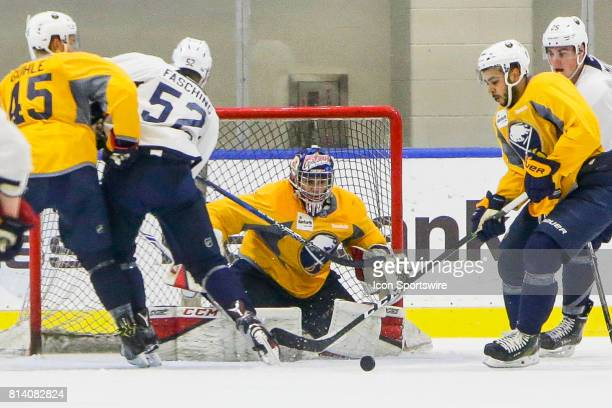 Buffalo Sabres Goalie Kyle Keyser tracks loose puck as Buffalo Sabres Defenseman Brendan Guhle Buffalo Sabres Right Wing Hudson Fasching and Buffalo...