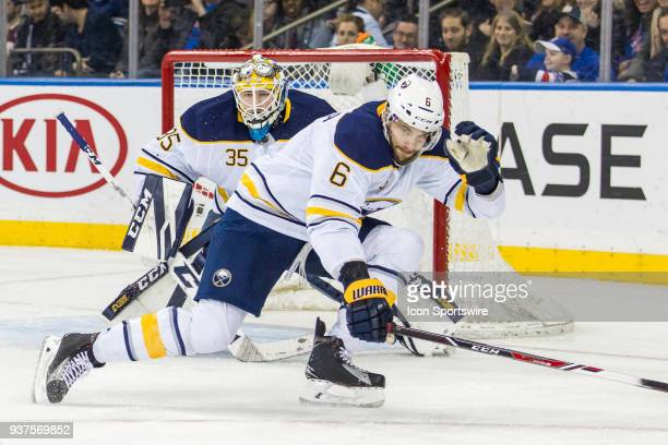 Buffalo Sabres Goalie Linus Ullmark peers over Defenceman Marco Scandella during the third period of a regular season NHL game between the Buffalo...