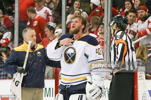 Buffalo Sabres goalie Robin Lehner of Sweden grimaces in pain after being hit in the neck with a stick during the third period of a regular season...