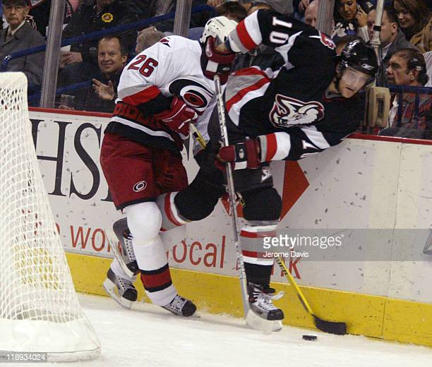 Buffalo Sabres' Henrik Tallinder is checked by Hurricanes' Erik Cole during a game against at the HSBC Arena in Buffalo, NY on November 09, 2005. The...