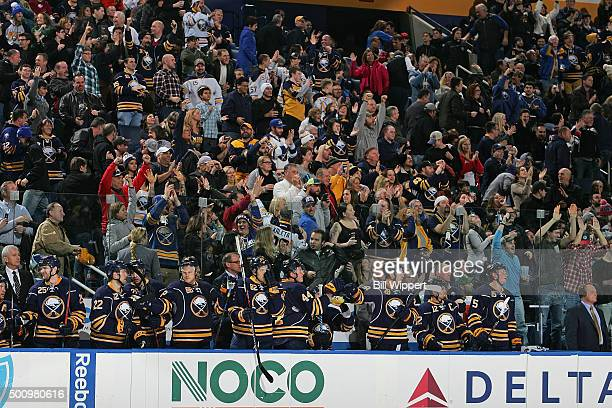 Buffalo Sabres players and fans cheer after a goal against the Arizona Coyotes during an NHL game on December 4 2015 at the First Niagara Center in...