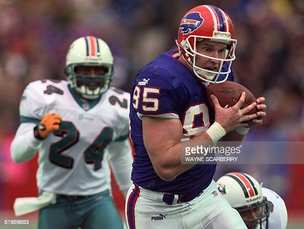 Buffalo tight end Jay Riemersma hauls in a pass from quarterback Doug Flutie as Miami cornerback Jerry Wilson pursues him downfield in the second...