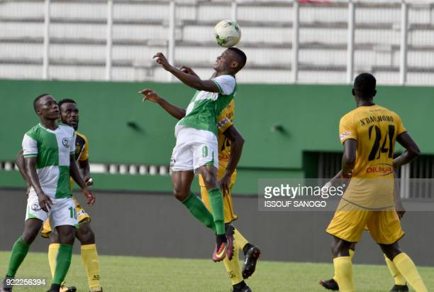 Buffaloes of Benin player Rodrigue Akossi heads the ball during the African Champions league football match between Asec d'Abidjan and Buffaloes of...