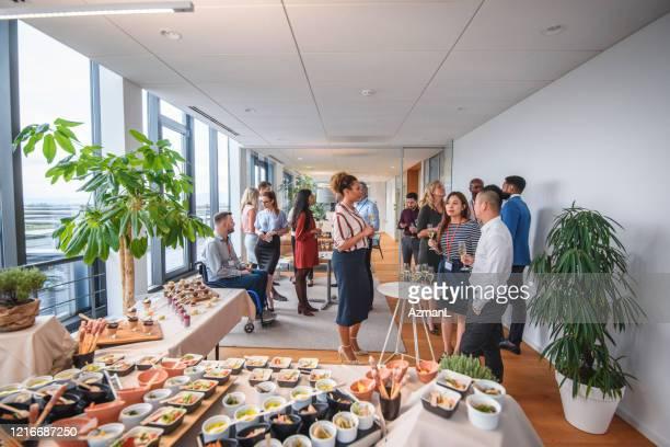 オフィスパーティーを楽しむ小料理や同僚のビュッフェ - バイキング形式 ストックフォトと画像