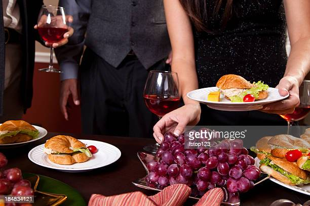 Buffet table. Appetizers, snacks. People eat holiday sandwiches. Wine. Party.