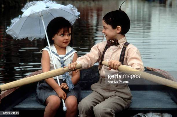 Bug Hall rowing a boat while looking at Brittany Ashton Holmes in a scene from the film 'The Little Rascals' 1994