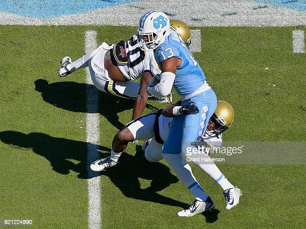 Bug Hoiward of the North Carolina Tar Heels makes a catch against Corey Griffin and Lawrence Austin of the Georgia Tech Yellow Jackets during the...