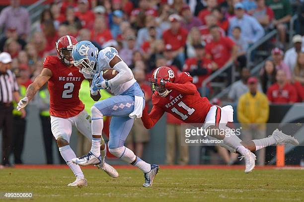 Bug Howard of the North Carolina Tar Heels makes a catch against Josh Jones and Juston Burris of the North Carolina State Wolfpack during their game...